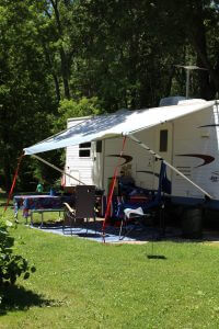 Phhoo of white camper with overhang and picnic table underneath.