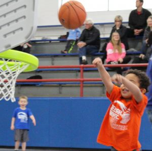 Young boy in orange shirt shooting at little tykes basket.