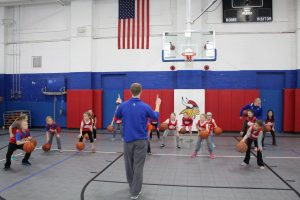 Group of kids dribbling basketballs.