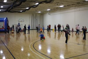 Children and adults playing games in gym