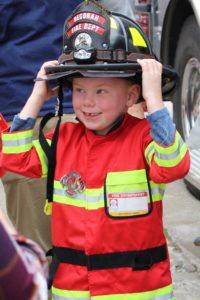 Little boy wearing fireman coat and hat