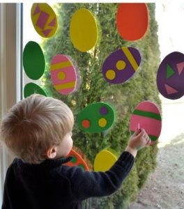 Boy decorating Easter eggs in windwo